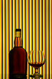 Brandy glass & bottle. A bottle of brandy and glass arranged against bright striped background Stock Photo