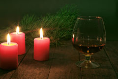 Brandy glass and candles on black background Royalty Free Stock Photos