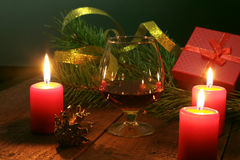 Brandy glass and candles on black background Royalty Free Stock Images