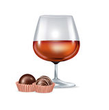 Brandy glass and chocolate candy Stock Photography