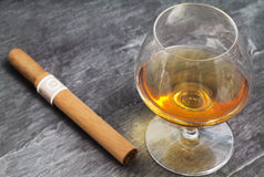Brandy glass and cigar over ardesia Stock Image