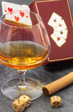 Brandy glass with dices, poker paper and cigar Royalty Free Stock Photography
