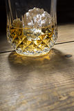 Brandy glass half full with ice cubes Stock Images