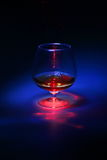 Brandy glass with red abstract and blue  light. Brandy glass with red abstract and blue light on black and blue background Stock Image
