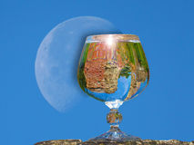 Brandy glass with water. On a background of the moon Stock Image