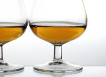 Brandy glasses. Two galsses of brandy against white background stock images