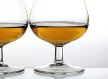 Brandy glasses. Two galsses of brandy over white background stock images