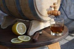 Brandy with lemon near oak barrel on a wooden table. A glass of brandy near an oak barrel with lemon on a wooden table royalty free stock images