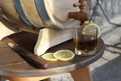Brandy with lemon near oak barrel on a wooden table. A glass of brandy near an oak barrel with lemon on a wooden table royalty free stock photos