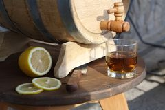 Brandy with lemon near oak barrel on a wooden table. A glass of brandy near an oak barrel with lemon on a wooden table royalty free stock photography