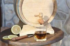 Brandy with lemon near oak barrel on a wooden table. A glass of brandy near an oak barrel with lemon on a wooden table stock image