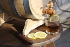 Brandy with lemon near oak barrel on a wooden table. A glass of brandy near an oak barrel with lemon on a wooden table royalty free stock photo