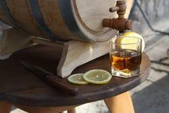 Brandy with lemon near oak barrel on a wooden table. A glass of brandy near an oak barrel with lemon on a wooden table stock photo