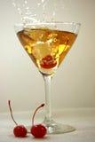 Brandy Manhattan Splash. Brandy Manhattan with maraschino cherry dropped into glass resulting in splash Royalty Free Stock Image