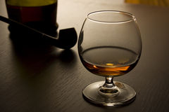 Brandy and pipe III. A glass with some brandy and pipe Stock Photography