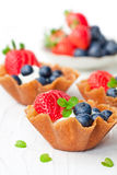 Brandy snaps baskets with soft cream cheese and berries on whit Stock Image