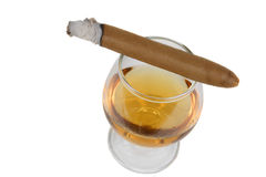 Brandy Sniffer and Cigar. Cigar with white ashes on a sniffer glass with brandy. Isolated on a white background Stock Photography