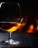 Brandy snifter warming before a glowing fire Royalty Free Stock Images