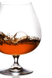 Brandy Splash. Snifter glass of cognac on white background Stock Photos