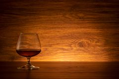 Brandy wine glass on wooden background. Cognac in a glass on a wooden table royalty free stock photo