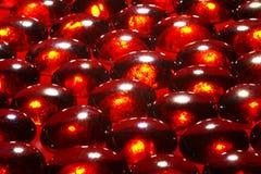 Branelli di vetro rossi su superficie rossa Fotografie Stock Libere da Diritti