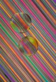 Branelli di vetro sulle paglie Fotografia Stock