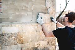 branscharbetare som installerar stentegelplattor på arkitektonisk husfasad arkivbild