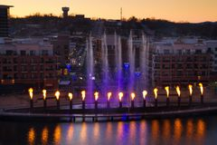 Branson Missouri Skyline at Sunset. Skyline view of Branson, Missouri with the display showing at the landing waterfront park area. The fountain has fire royalty free stock photo