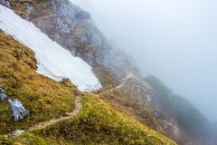 Brant bergpasserande som går in i molnet Arkivfoto