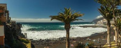 Brant h?g lava vaggar klippor Turkoshavet vilar på en ljus blå himmel och en linje av moln ovanför horisonten Playa arenastrand royaltyfri fotografi
