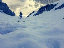 Brant iskall lutning med den suddiga alpinisten royaltyfria foton