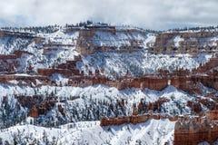 Brant kanjonvägg med olycksbringare, träd och snö, Bryce Canyon Royaltyfria Bilder