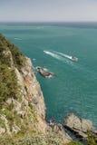 Brant klippa, hav och en motorbåt som beskådas från över royaltyfri foto