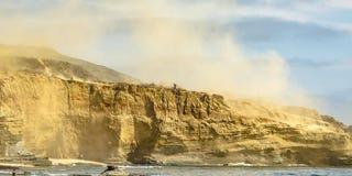 Brant klippa med damm mot himmel i det La Jolla havet arkivbild
