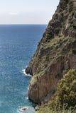 Brant klippa som stiger ned till havet Arkivbild