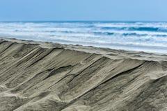 Brant kulle av sand bredvid havvågor Arkivfoto