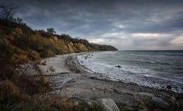 Brant kust med stranden, stenar och vågor under en mörk molnig himmel på Östersjön i Mecklenburg-västra Pomerania, Tyskland, kopi royaltyfria bilder
