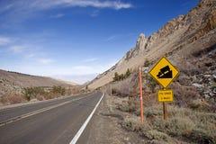 Brant sluttande på en bergväg arkivbilder
