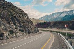 Brant vänd av vägen på det slingrande berget Berglandskap av det Chui området, Altai Dal Chuya royaltyfri fotografi