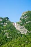 Branta klippor som täckas i träd med den avlägsna vattenfallet under blått Royaltyfria Bilder