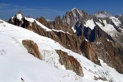 Branta klippor som täckas med insnöat de schweiziska fjällängarna Royaltyfri Fotografi