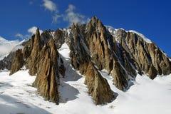Branta klippor som täckas med insnöat de schweiziska fjällängarna Arkivfoton