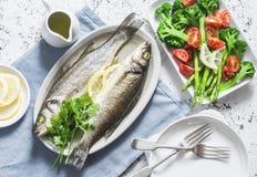 Branzino al forno e verdure - broccoli, asparago, pomodori su un fondo leggero, vista superiore Pasto equilibrato sano fotografia stock libera da diritti