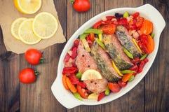 Branzino con le verdure pesce marinato con le verdure per la cottura nel forno Priorità bassa di legno Vista superiore Primo pian immagini stock