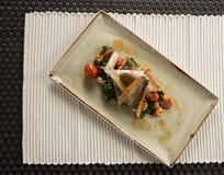 Branzino fritto con il gambero, il chorizo, gli spinaci del bambino & i pomodori ciliegia Fotografia Stock