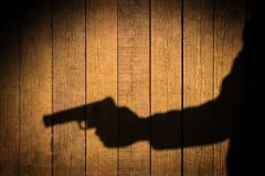 Braço estendido com uma arma. Sombra preta no fundo de madeira. Fotos de Stock Royalty Free