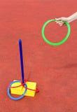 Braço que joga anéis coloridos em torno do polo Fotografia de Stock Royalty Free