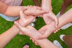 Bras avec des mains des filles se tenant s Photos libres de droits