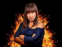 Bras croisés fâchés de femme de brune entourant par le feu Images libres de droits