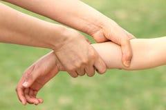 Bras d'enfant de loquet de mère images libres de droits
